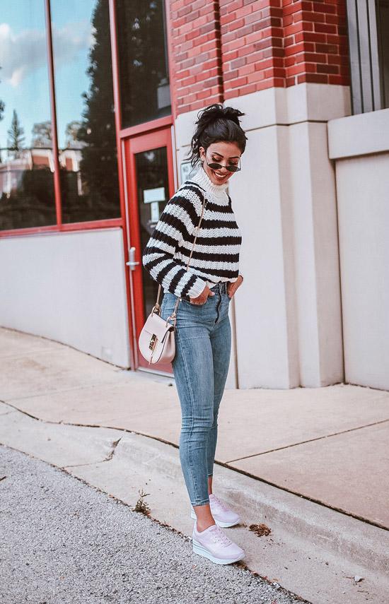 Девушка в облегающих джинсах и свитер в полоску