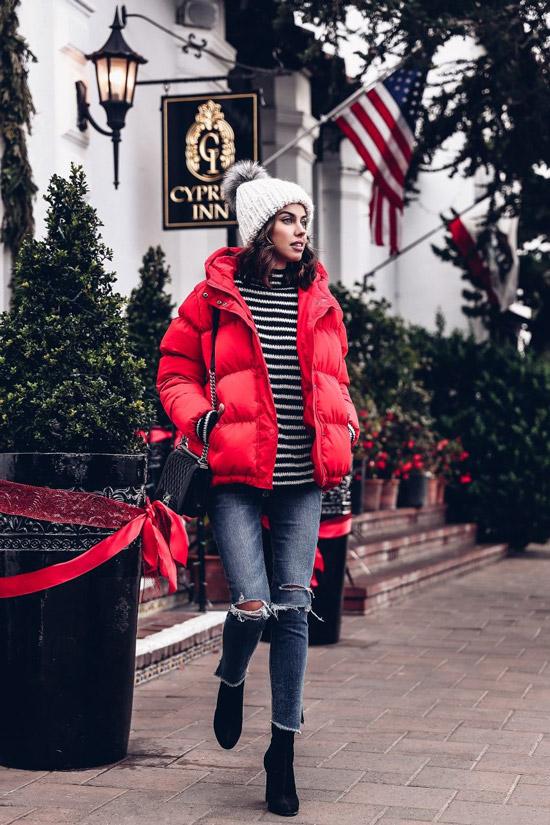 Девушка в рванных джинсах, свитер в полоску и красный пуховик