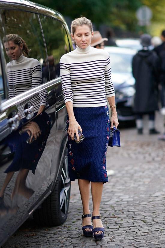 Девушка в синей юбке миди, белый свитер в полосу и босоножки