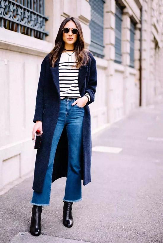 Девушка в синих джинсах клеш, белый свитшот в полоску и синее пальто