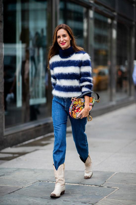 Девушка в синих джинсах, пушистый полосатый свитер и ковбойские сапоги