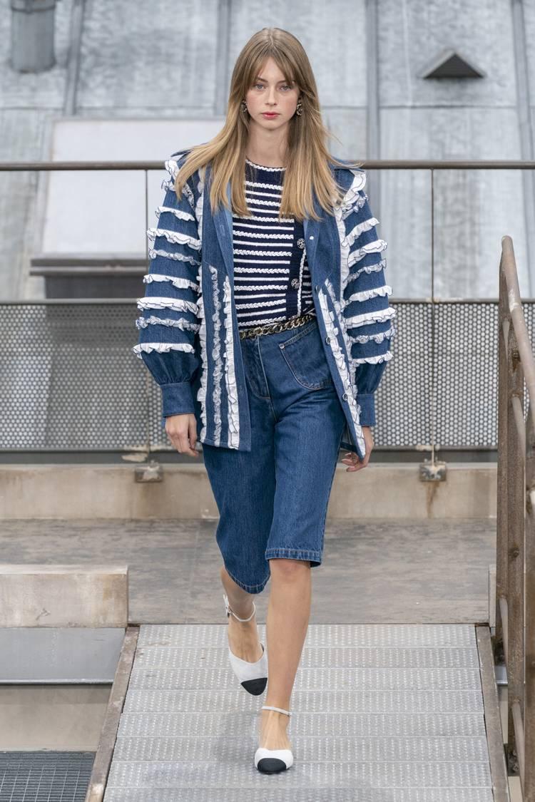 Девушка в синих джинсовых бермудах, топ в полоску и синяя джинсовая куртка