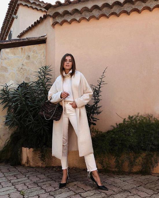 Девушка в укороченных белых джинсах, свитер и пальто молочного цвета