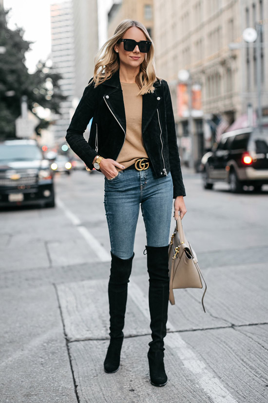 Девушка в узких джинсах с ремнем, замшевые ботфорты и куртка косуха