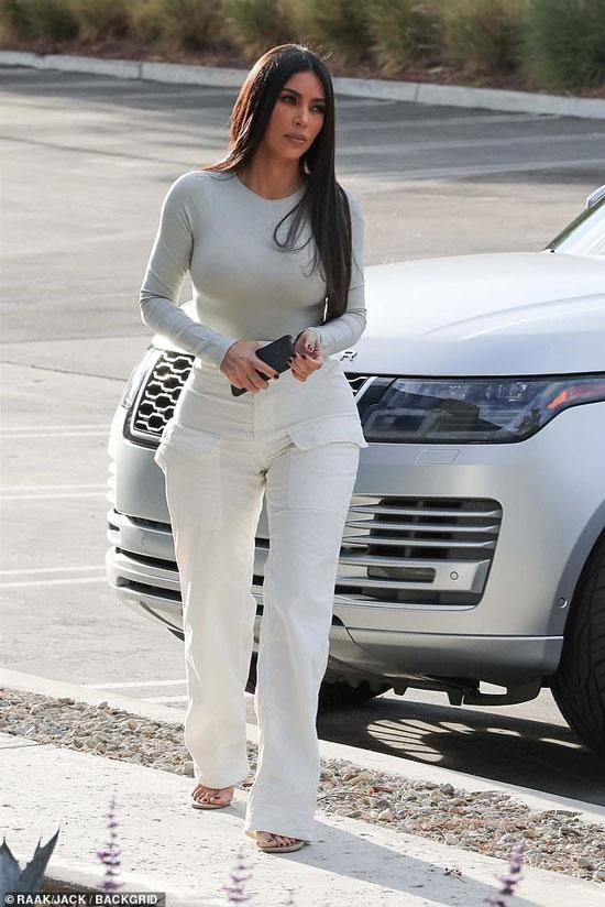 Ким Кардашьян в белых брюках с накладными карманами и сером боди