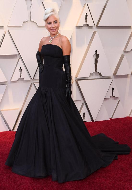 Леди Гага в черном длинном платье и высокие перчатки