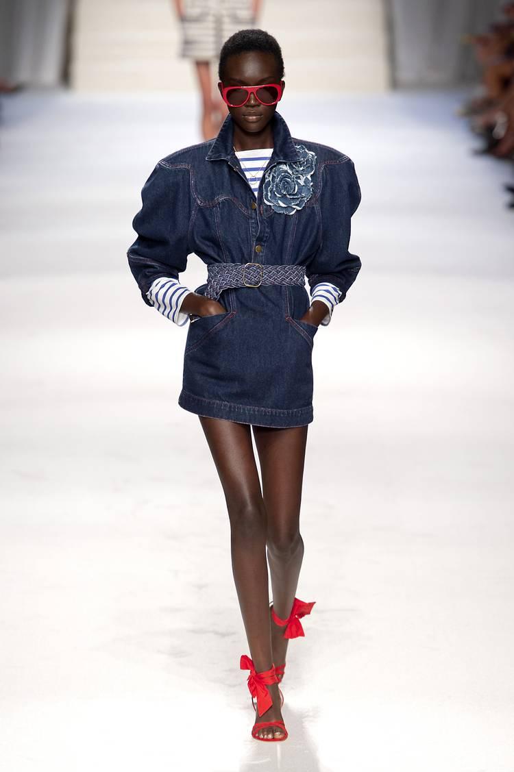 Модель в джинсовом платье мини с ремнем и объемными рукавами, красные босоножки