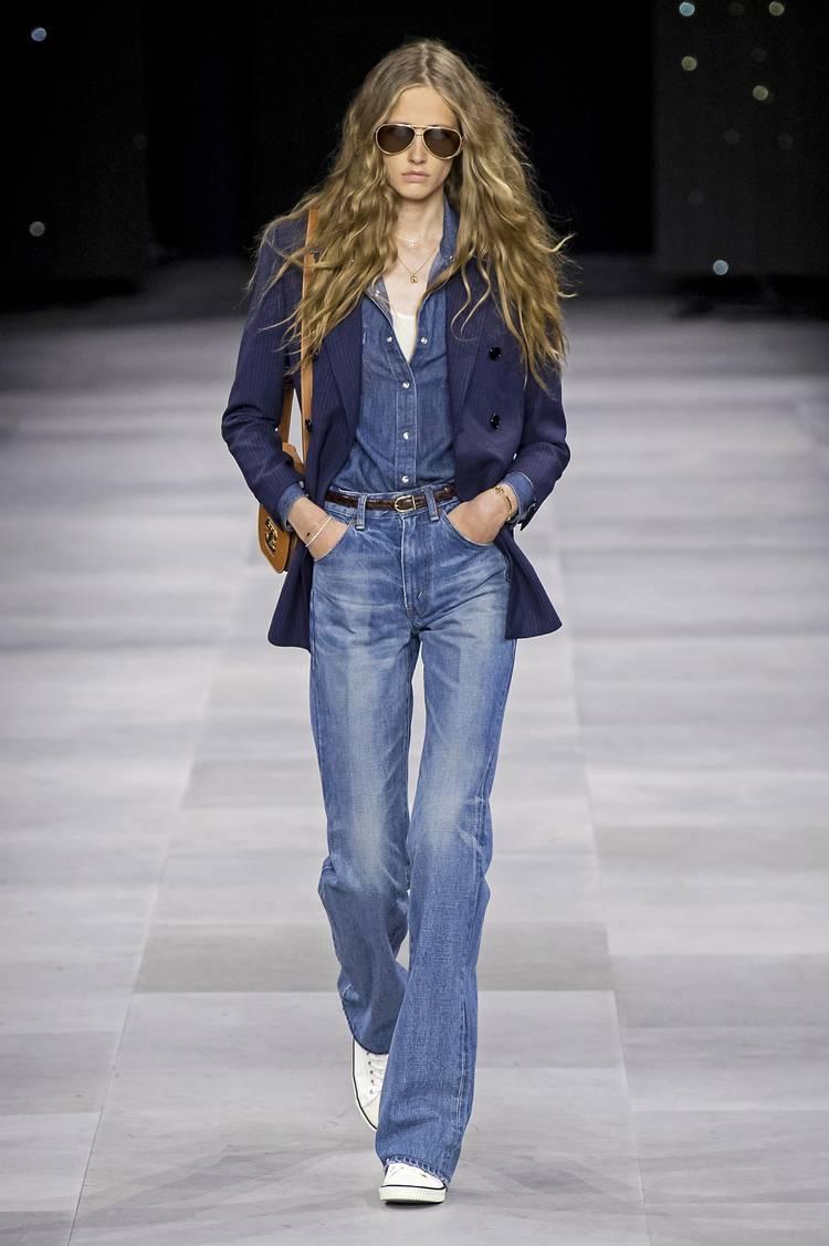 Модель в синих джинсах, джинсовая рубашка и белые кеды