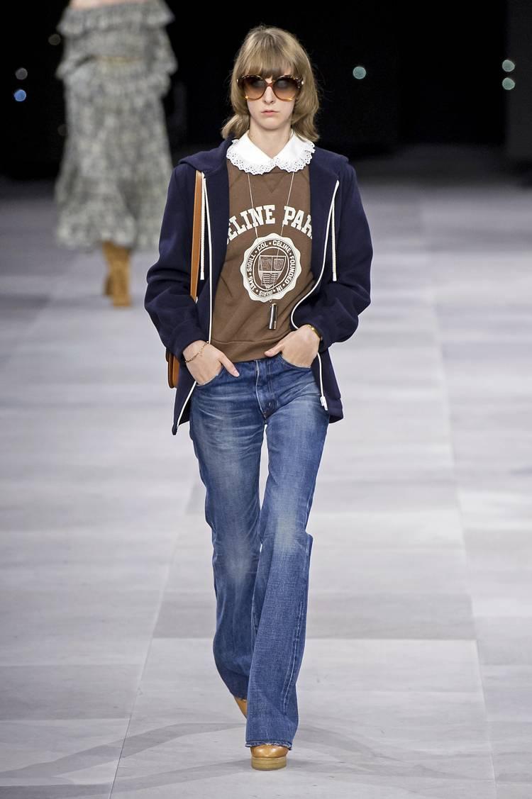 Модель в синих джинсах клеш, коричневая толстовка и темная кофта