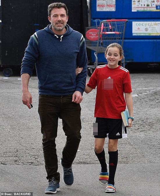 Бен Аффлек в синей толстовке, кроссовках и джинсах цвета хаки