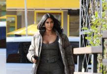 Ким Кардашьян в монохромном образе: спортивные брюки дополняются ботильонами и пуховиком
