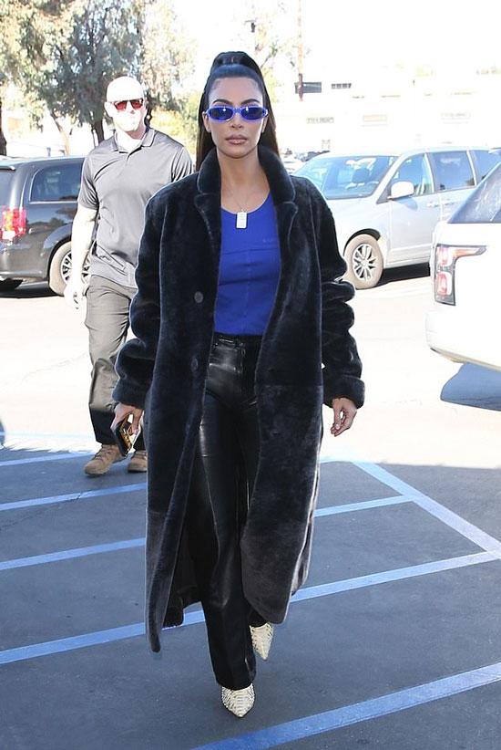 Ким Кардашьян в кожаных брюках, синем топе и плюшевом пальто