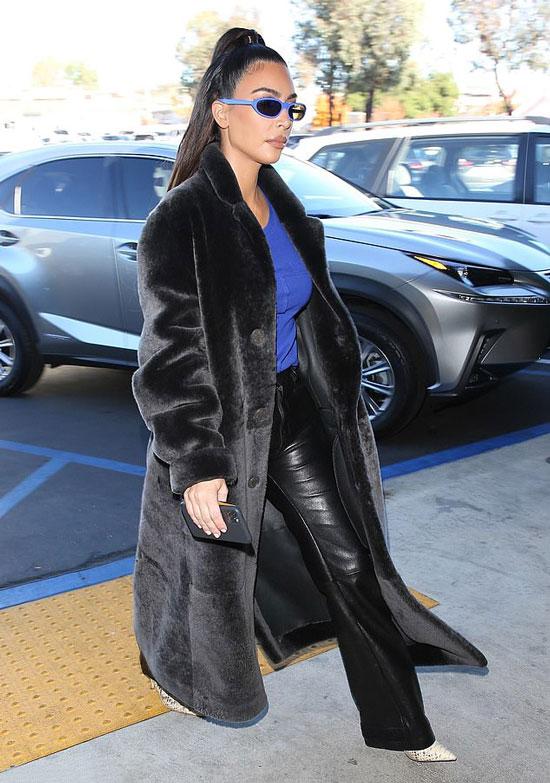 Ким Кардашьян в кожаных брюках, синем топе, очках и плюшевом пальто