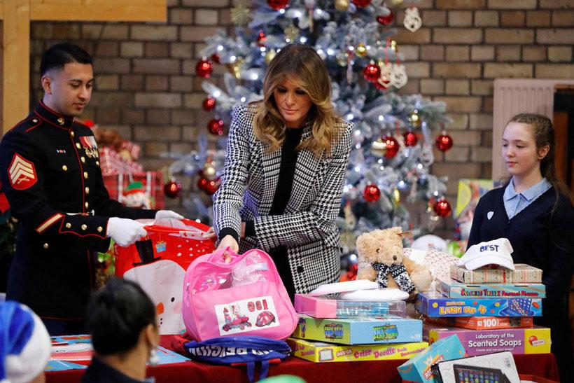 Мелания Трамп в черно-белом пальто упаковывает подарки