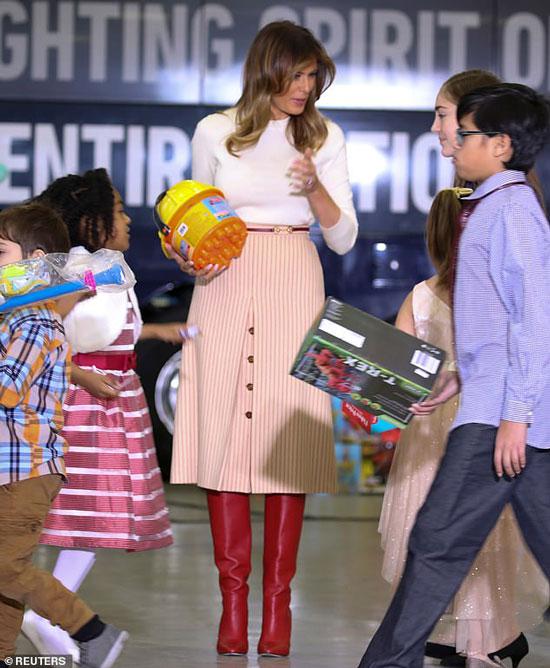Мелания Трамп в белом джемпере и юбке в полоску
