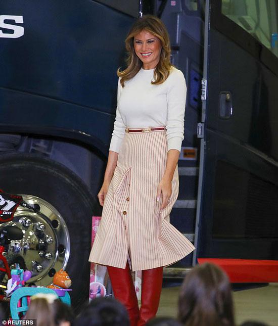 Мелания Трамп в белом джемпере, юбке в полоску и красных сапогах