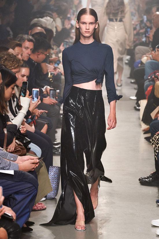 Модель в виниловых брюках клеш и футболке с узелками