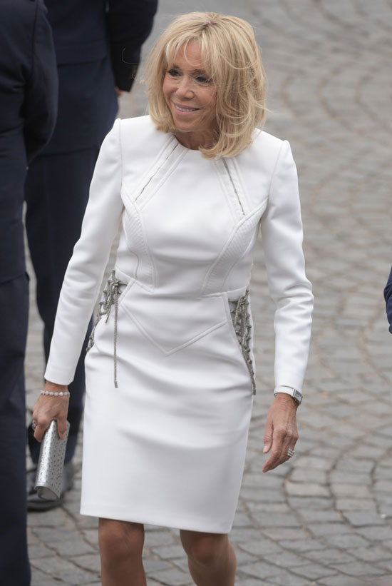 Брижит Макрон в белом платье с завязками по бокам и серебристым клатчем 14 июля 2019
