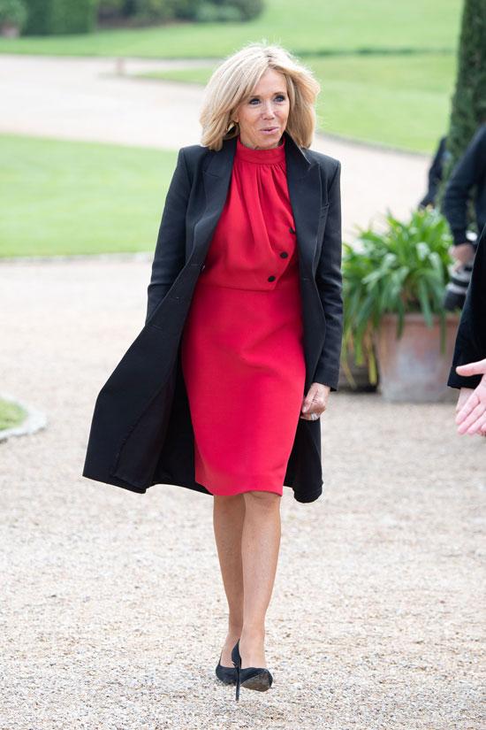Брижит Макрон в красном платье и черном пальто 2 мая 2019