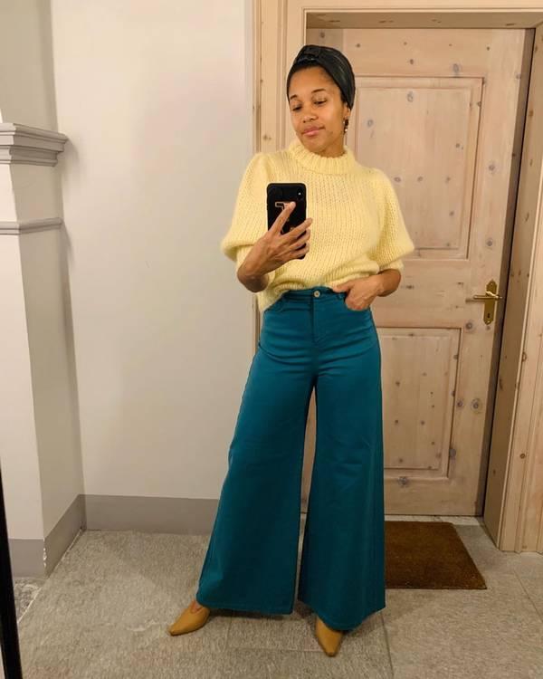 Девушка в бирюзовых широких брюках и светло-желтый свитер