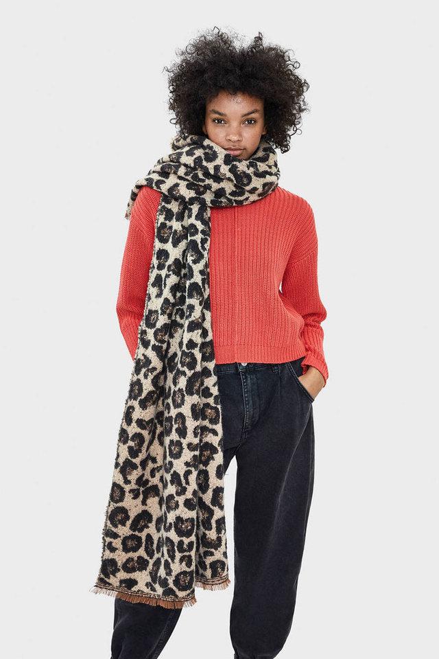 Девушка в черных джинсах, красный свитер и леопардовый шарф