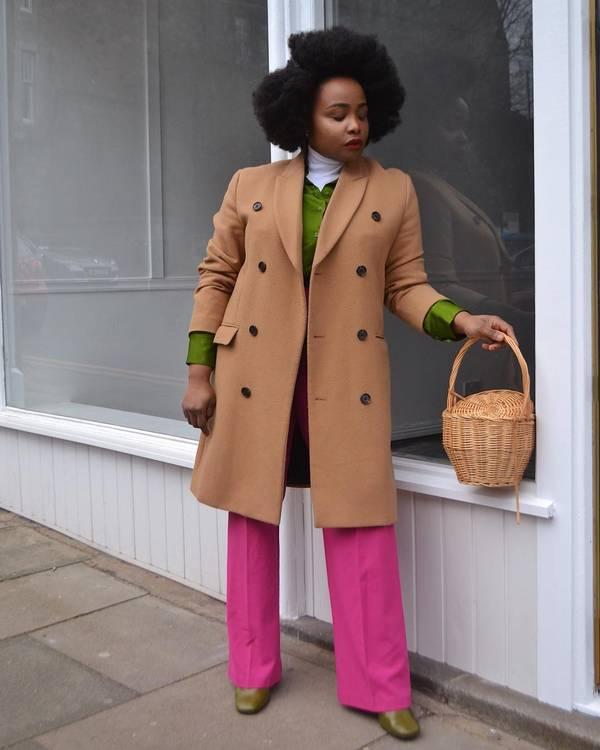 Девушка в бежевом пальто, розовые брюки клеш и зеленый свитер