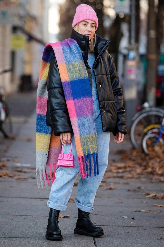 Девушка в джинсах, черный пуховик и разноцветный шарф