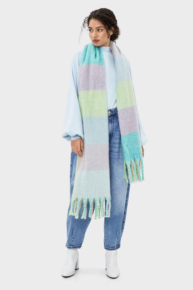 Девушка в голубых джинсах, белая водолазка и пастельный шарф оверсайз