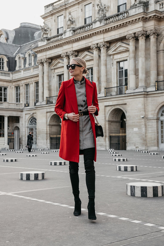 Девушка в красном пальто, черные ботфорты и блейзер в клетку с ремнем