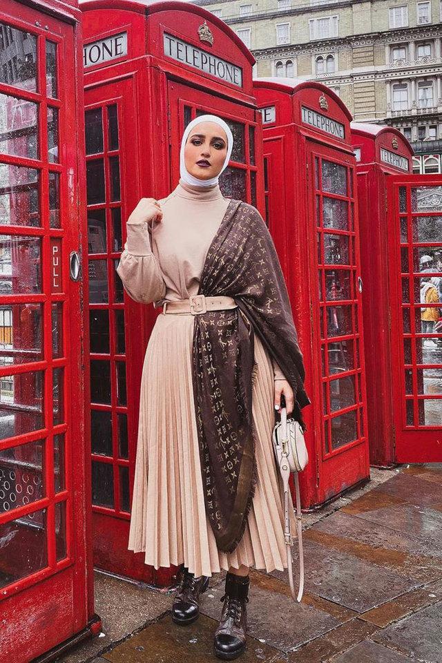 Девушка в плиссированной юбке миди с ремнем и коричневый платок