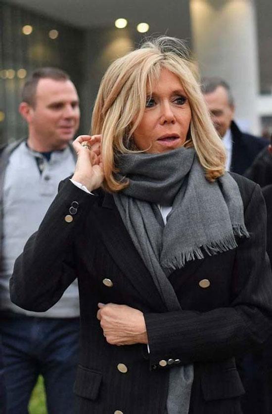 Брижит Макрон в длинном жакете и стильном сером шарфике, завязанном на шее