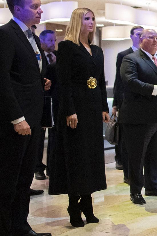 Иванка Трамп в длинном черном пальто с золотым цветком на поясе и сапогах на шпильке