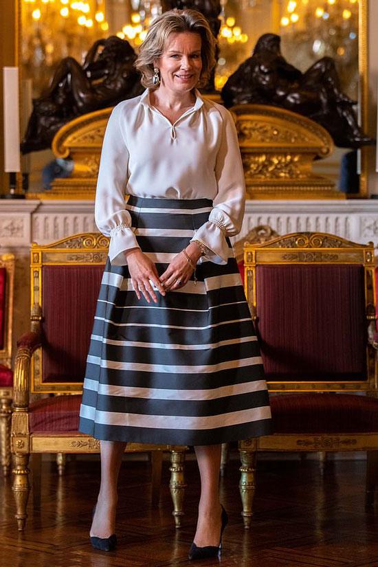 Бельгийская королева Матильда в белой шелковой блузе с манжетами и юбке миди в полоску