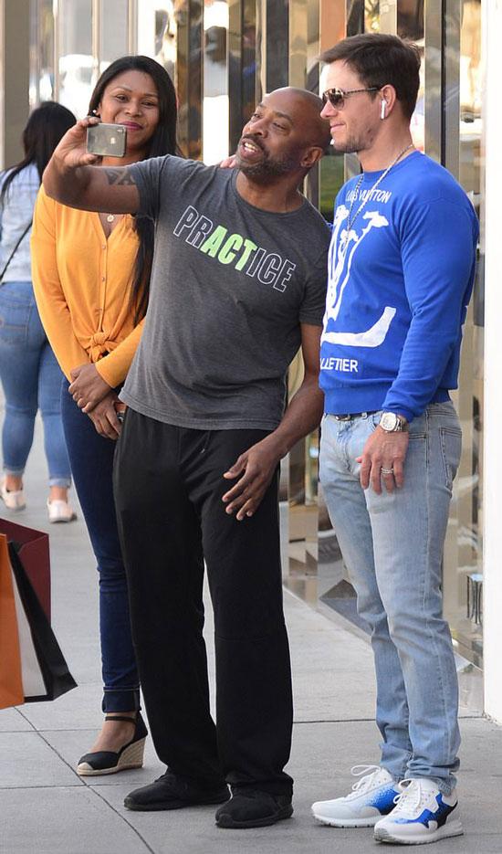 Марк Уолберг в синем свитшоте, джинсах и белых кроссовках