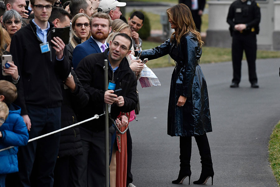 Мелания Трамп в виниловом черном плаще и ботфортах