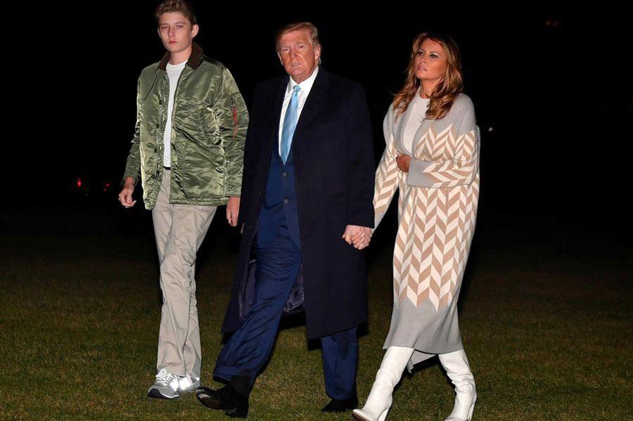 Мелания Трамп в белых сапогах и светлом пальто с принтом