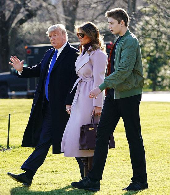 Мелания Трамп в сиреневом пальто и темно-красных сапогах
