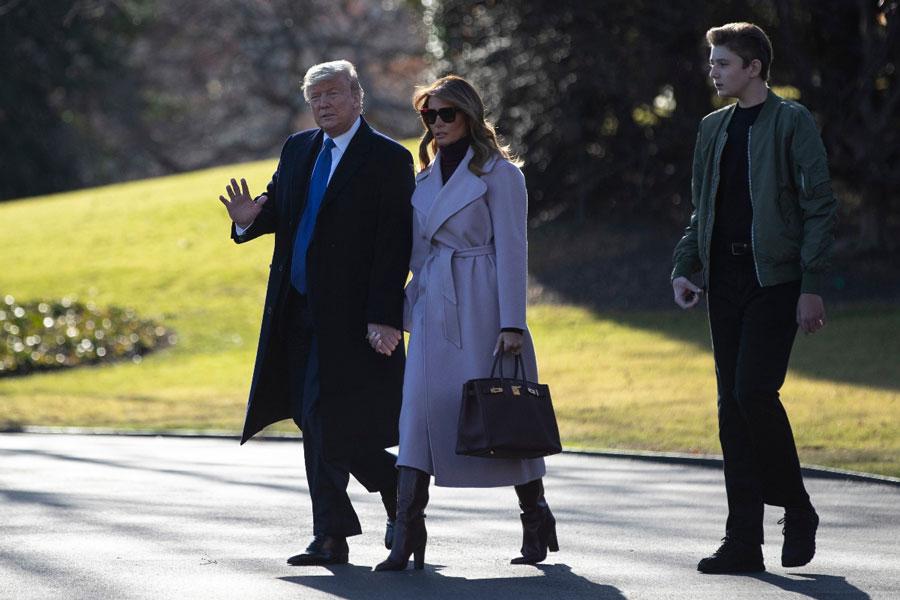 Мелания Трамп в сиреневом пальто, сапогах трубах и водолазке