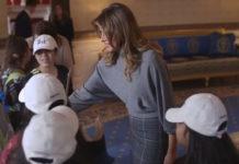 Мелания Трамп улыбается, принимая гостей из начальной школы. На ней юбка-миди и водолазка