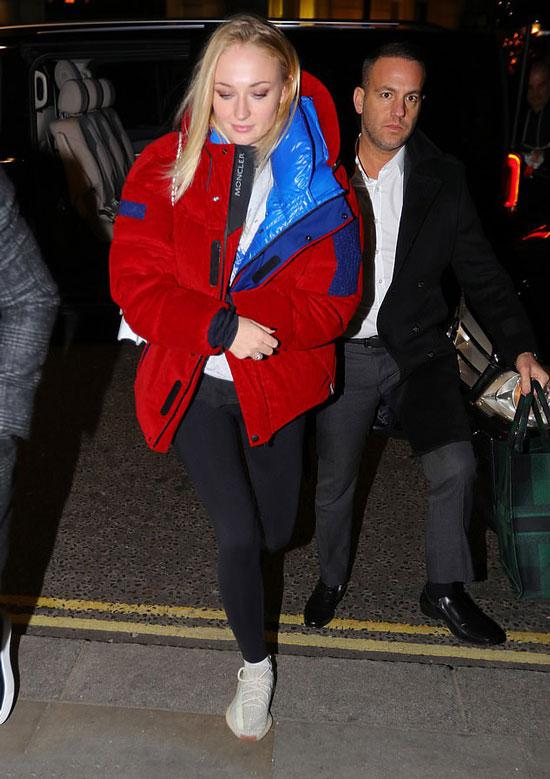 Софи Тернер в красной оверсайз-куртке и черных леггинсах