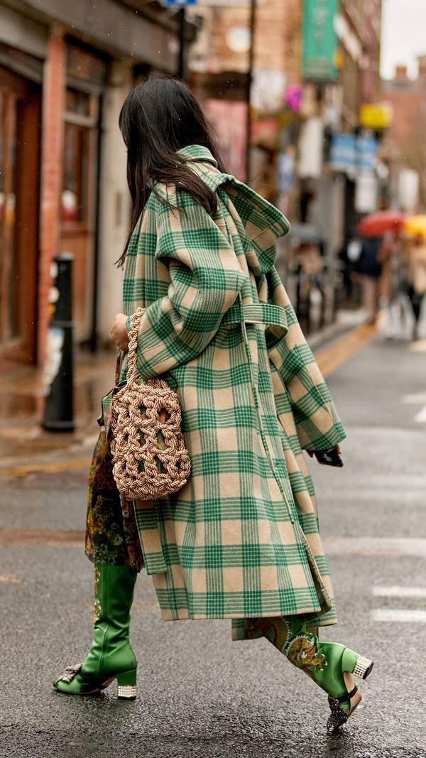 Девушка в бежево-зеленом пальто в клетку, необычные зеленые сапоги и сумка