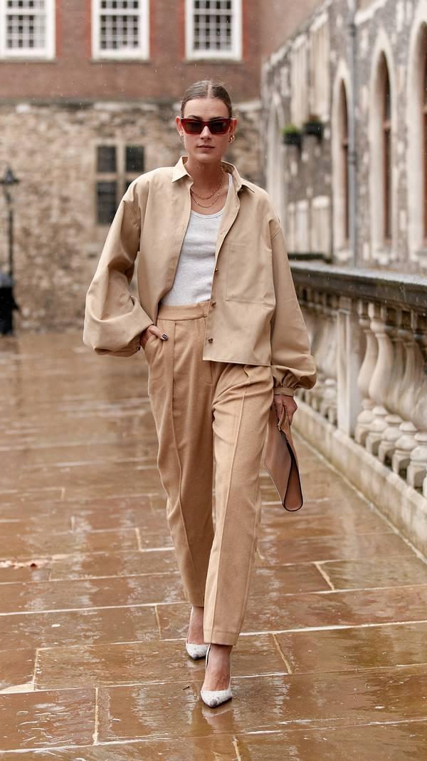 Девушка в бежевых брюках, топ и куртка оверсайз, белые туфли лодочки