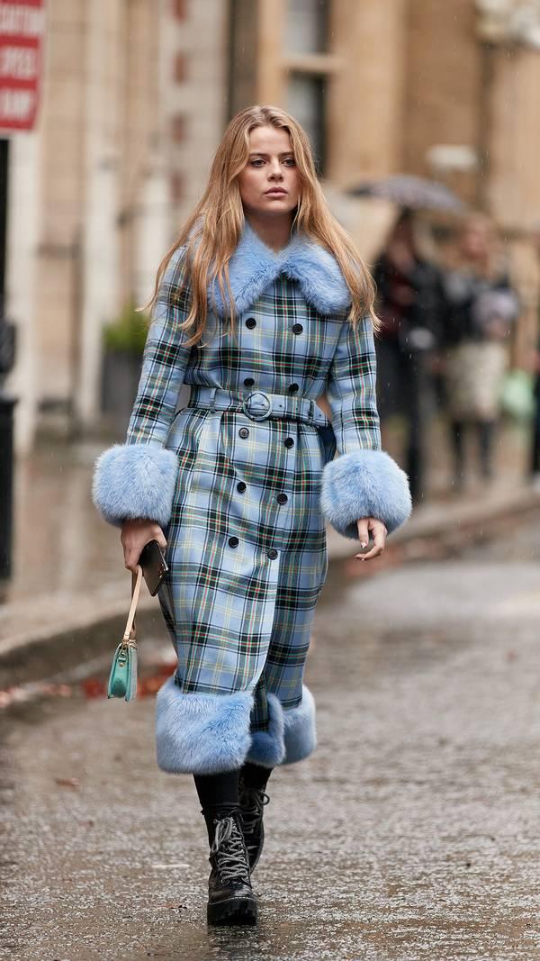 Девушка в голубом пальто в клетку с меховой отделкой и черные ботинки