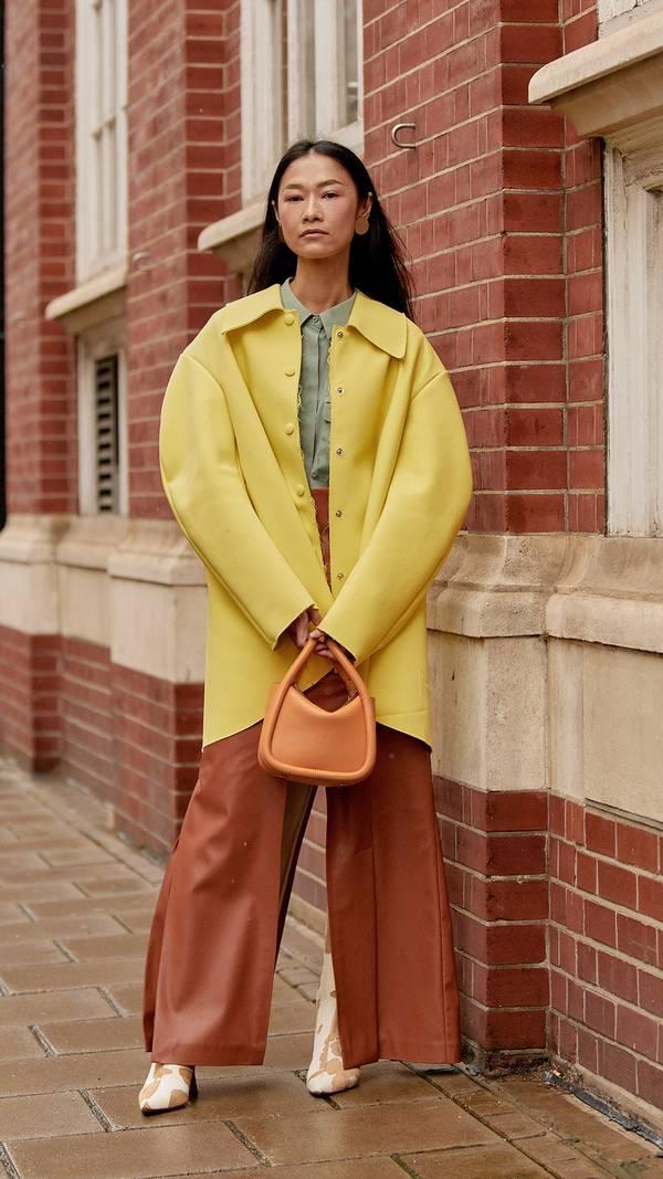 Девушка в коричневых широких брюках, желтый плащ и ботильоны