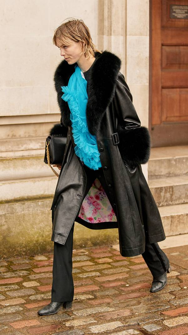 Девушка в кожаном плаще с меховым воротником и манжетами, черные брюки и ботильоны