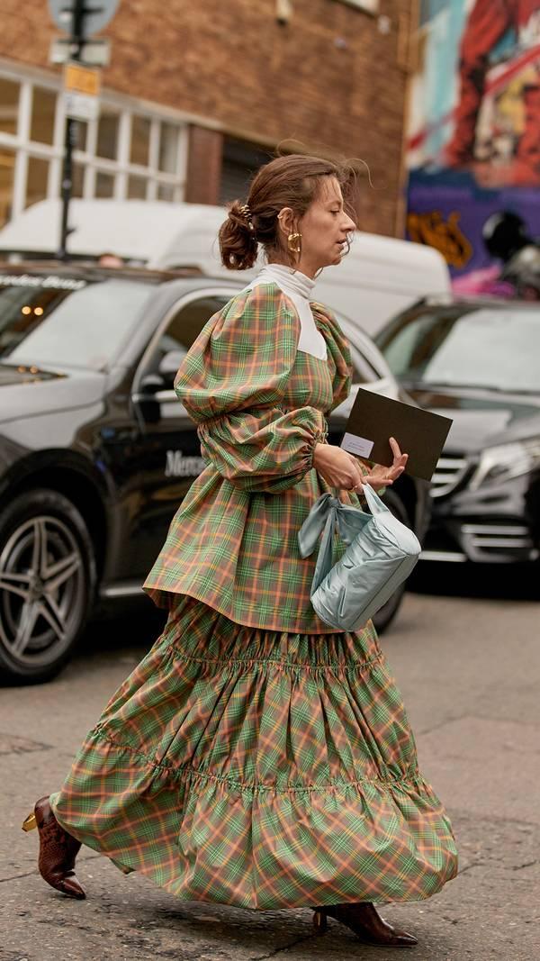 Девушка в необычном воздушном платье в клетку зеленого цвета и коричневые ботильоны