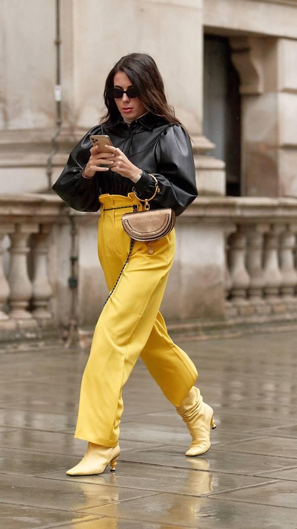 Девушка в прямых желтых брюках с завышенной талией, черная кожаная рубашка и желтые сапоги