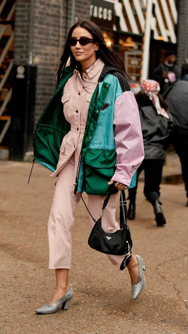 Девушка в розовом брючном костюме, зеленый жилет оверсайз и серебристые туфли
