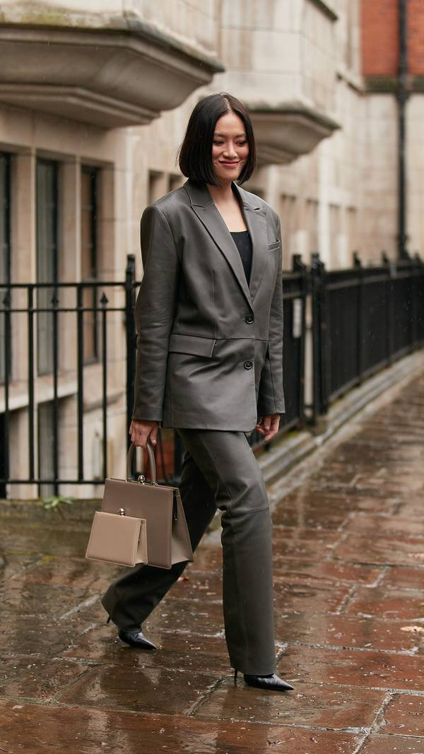 Девушка в сером кожаном костюме, черный топ и туфли на шпильке