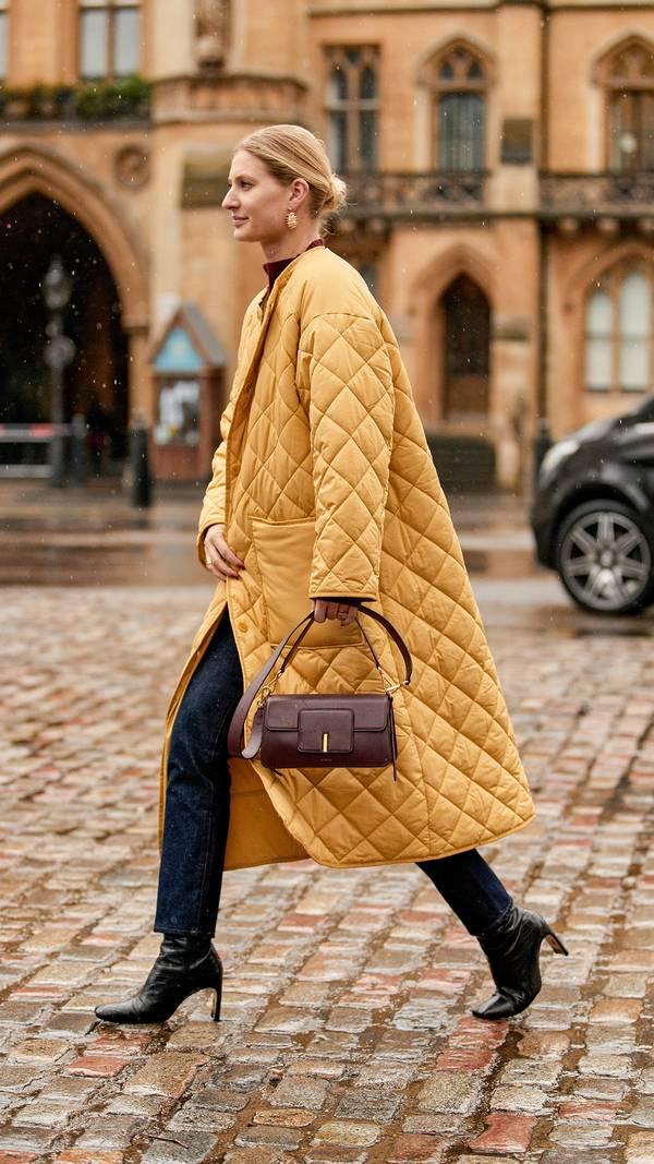Девушка в желтом стеганном пальто, узкие джинсы и черные ботильоны